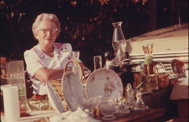 Image: Older woman at a table with vintage plates and sales