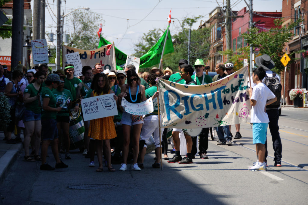Marchers holding signs marching in the Mad Pride Parade in Toronto 2016